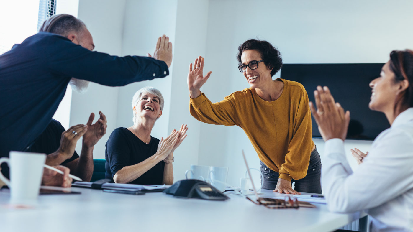 Woman and man high five across a table after a business meeting